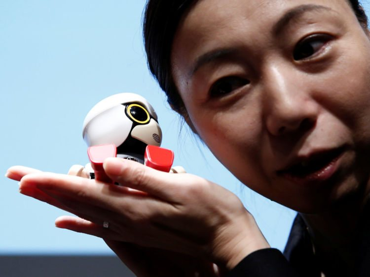 A staff member listens to Toyota Motor Corp's Kirobo Mini robot's voice as she poses with the robot after a news conference in Tokyo, Japan, September 27, 2016. Picture taken on September 27, 2016.REUTERS/Kim Kyung-Hoon - RTSQH3E